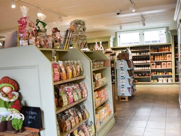 Gårdsbutik med hyllor fyllda med lokala produkter på Axelsson i Aby