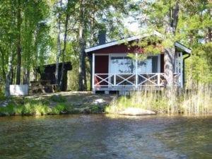 En bild på en röd stuga med en liten altan. Bredvid huset finns en liten grillplats med en bänk att sitta vid och en flod.