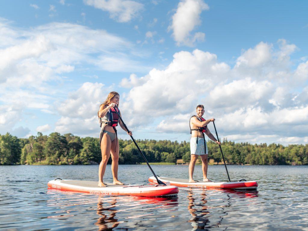 Двоје људи на дасци за веслање на језеру