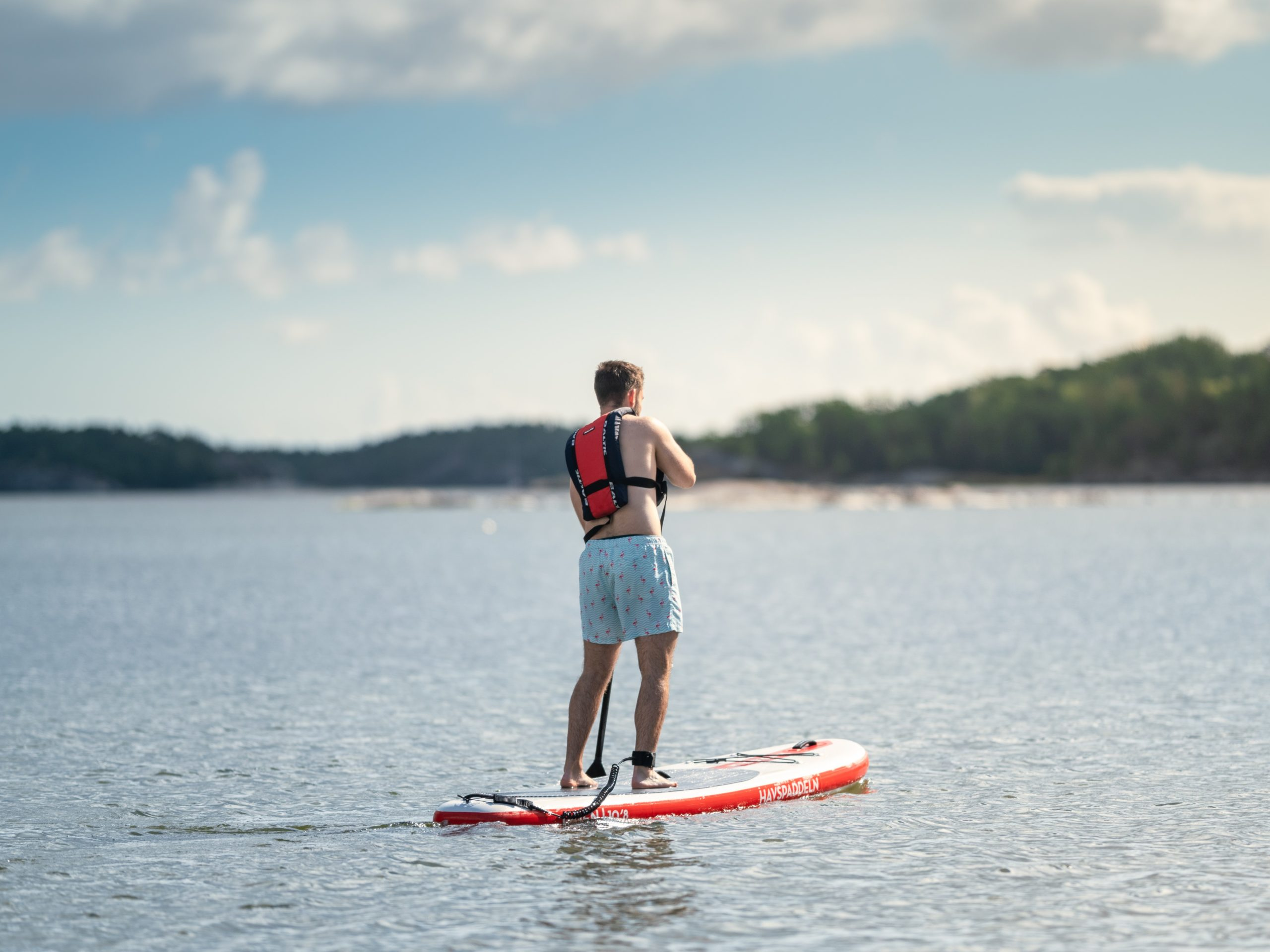 Kille på paddleboard ute på sjön