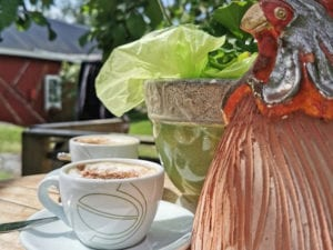 En bild på ett bord på nära håll, på bordet finns två små tallrikar med koppar på och vid sidan om en höna gjord av porslin.