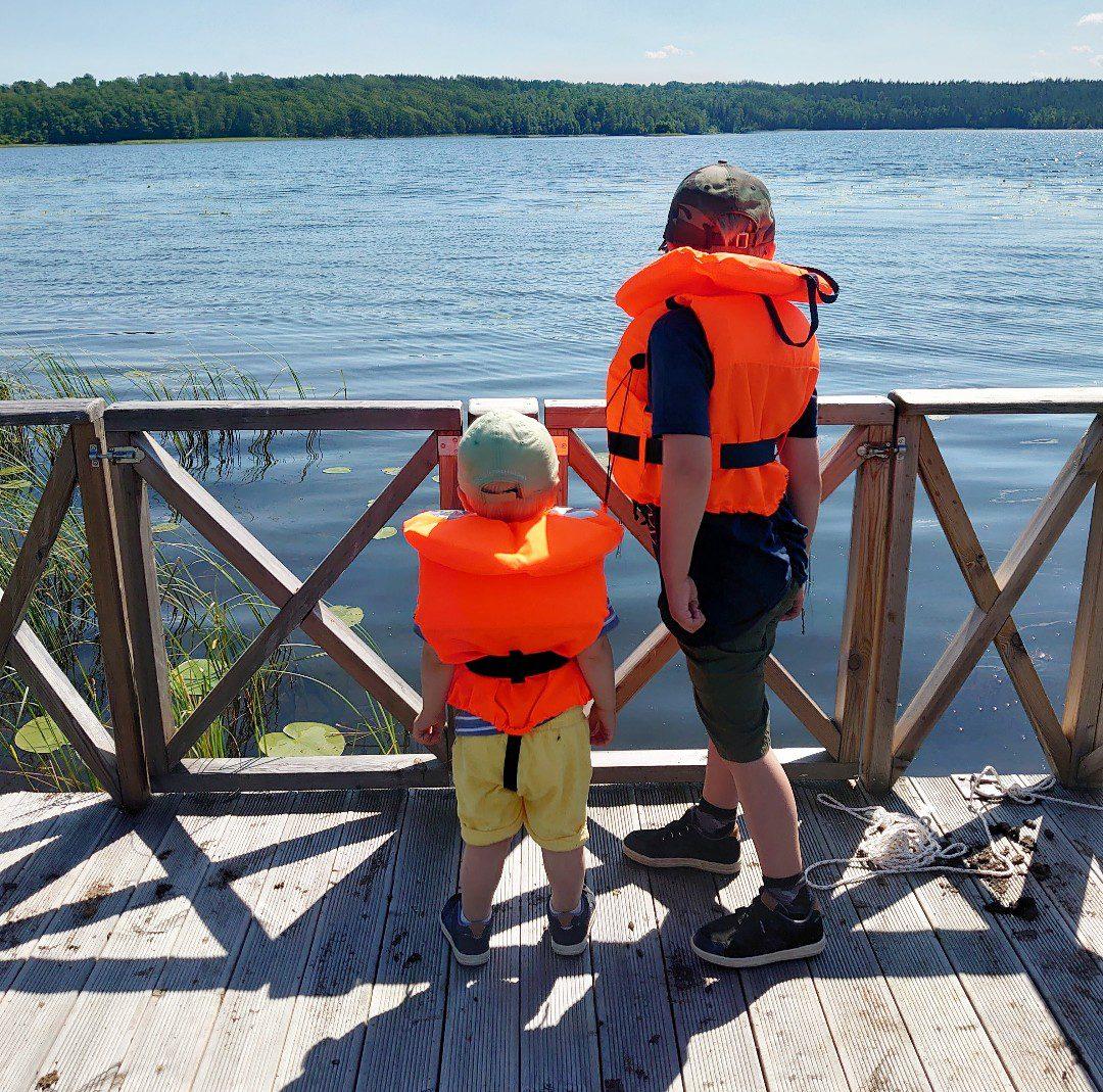 Barn med flytväst vid en sjö