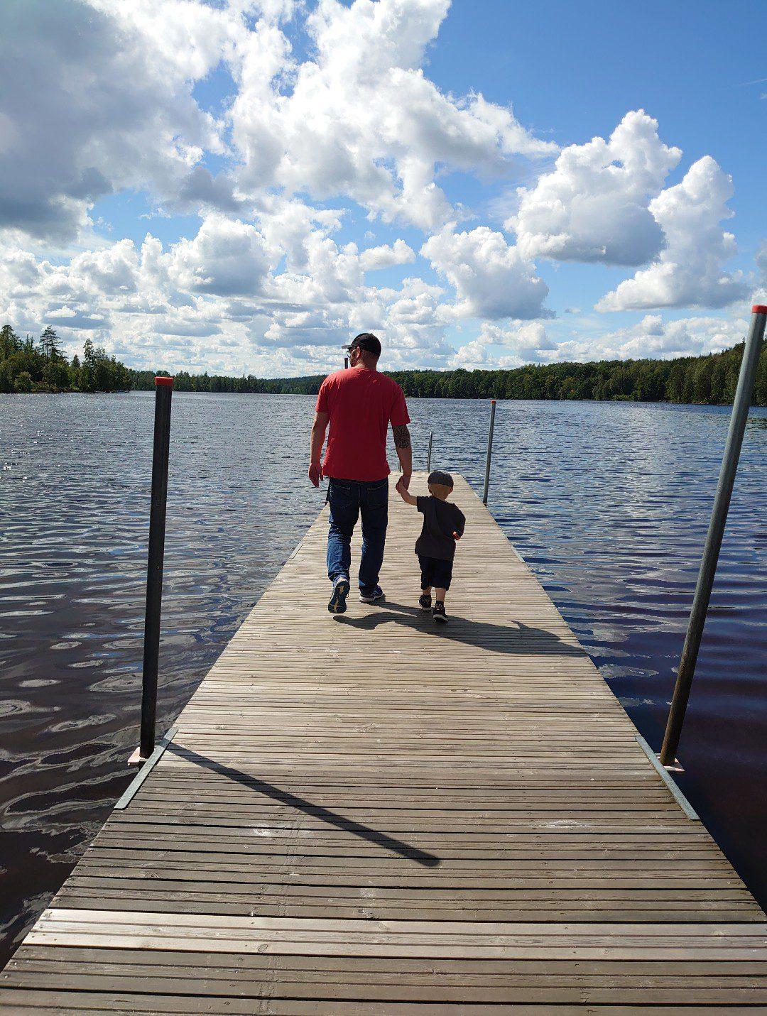 Pappa och son på brygga en sommardag