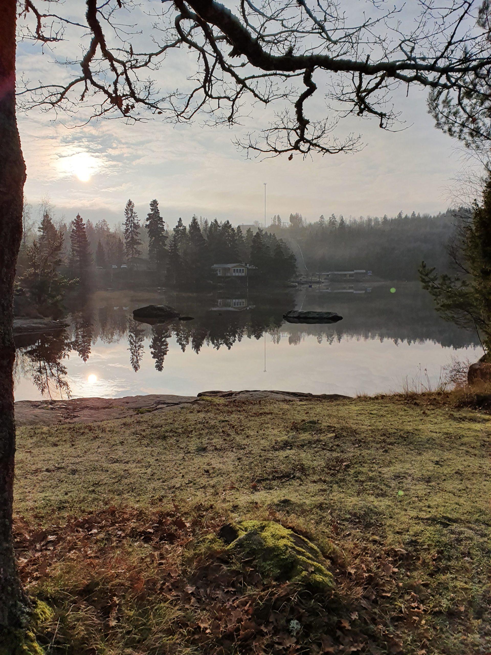 Disig sjö med skymt av hus
