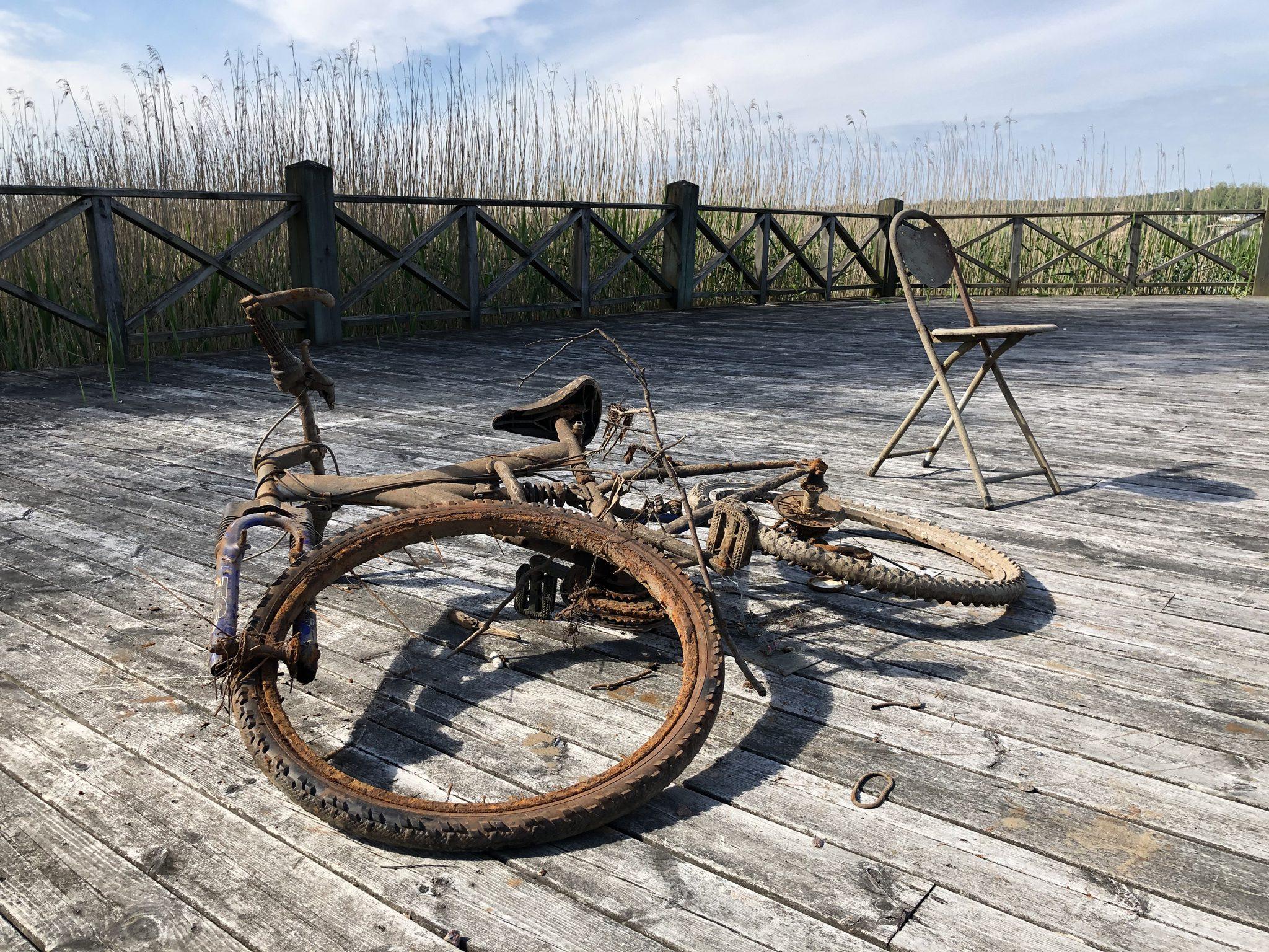 Rostig cykel och stol på stort trädäck